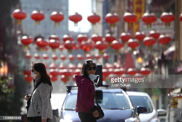 People wear surgical masks as they walk along Chinatown's Grant Avenue on February 26, 2020 in San Francisco, California. San Francisco Mayor London...