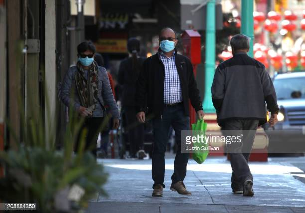People wear surgical masks as they walk along Chinatown's Grant Avenue on February 26 2020 in San Francisco California San Francisco Mayor London...