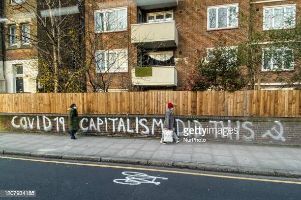 People wear surgical masks as they walk past a graffiti reading Covid19 capitalism did this in East London on March 21 2020 in London England...