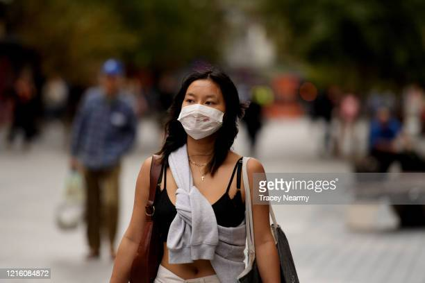 People wear surgical masks in Adelaide on April 01 2020 in Adelaide Australia The Australian government has introduced further restrictions on...