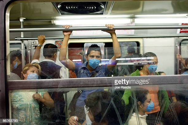 People wear surgical masks to help prevent being infected with the swine flu as they ride the subway on April 28 2009 in Mexico City Mexico Reports...