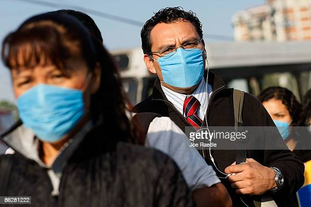 People wear surgical masks to help prevent being infected with the swine flu as they wait for a public bus on April 29 2009 in Mexico City Mexico...
