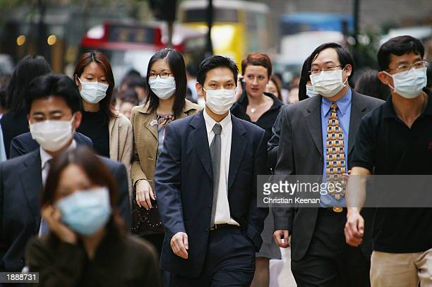 People wear surgical masks to try to reduce the chance of infection from SARS whilst walking through the business district April 1, 2003 in Hong...