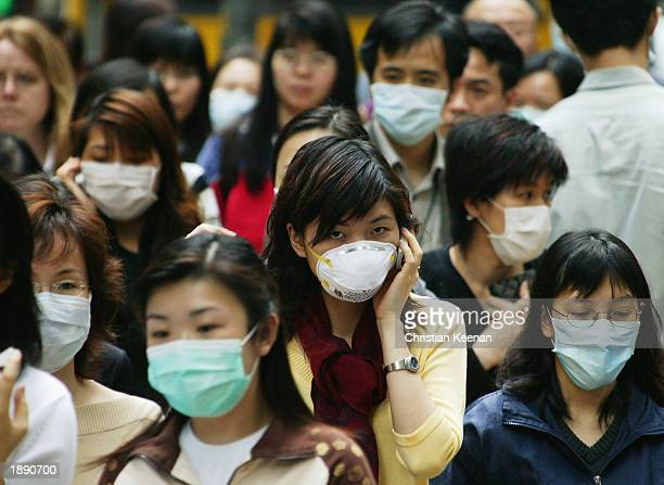 People wear surgical masks to try to reduce the chance of infection from SARS whilst walking through the business district April 1 2003 in Hong Kong...