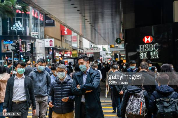 People wear surgical masks while crossing the road as a preventative measure following the Coronavirus outbreak which began in the Chinese city of...