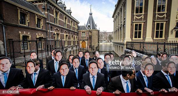 People wear the same mask picturing Dutch Prime Minister Mark Rutte during a demonstration against farm animals cloning on March 8 2016 in The Hague...