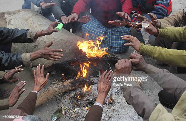 People wear warm clothes and sit around a bonfire to protect themselves from the cold on cold foggy and chilly morning in Allahabad on Wednesday Low...