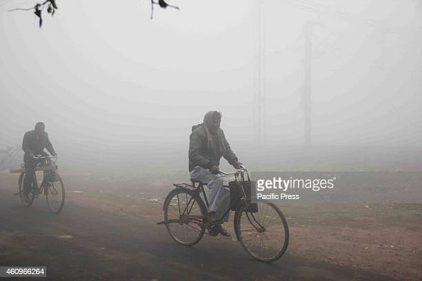People wear warm clothes to protect themselves from cold winds on a cold foggy and chilly morning in Allahabad on Tuesday Many people died due to a...