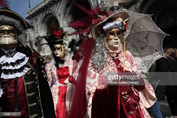 People wearing a Carnival mask pose in San Marco square during the Venice Carnival 2020 on February 16, 2020 in Venice, Italy.