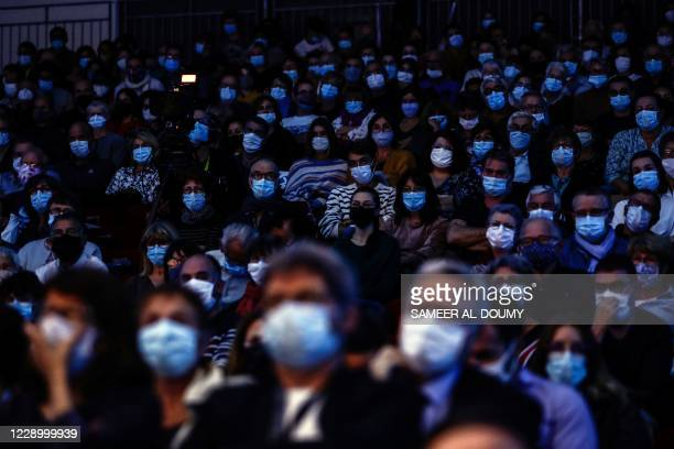 People wearing a face mask attend the closing ceremony of the 2020 Prix Bayeux-Calvados Awards for war correspondents in Bayeux, northwestern France,...