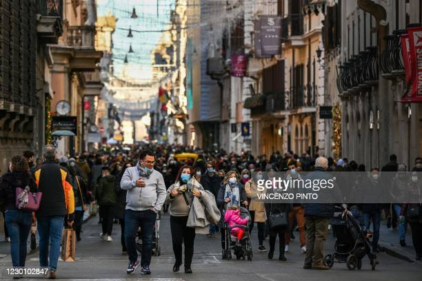 People wearing a face mask gather on the Via del Corso main street for their Christmas shopping on December 13, 2020 in downtown Rome, during the...