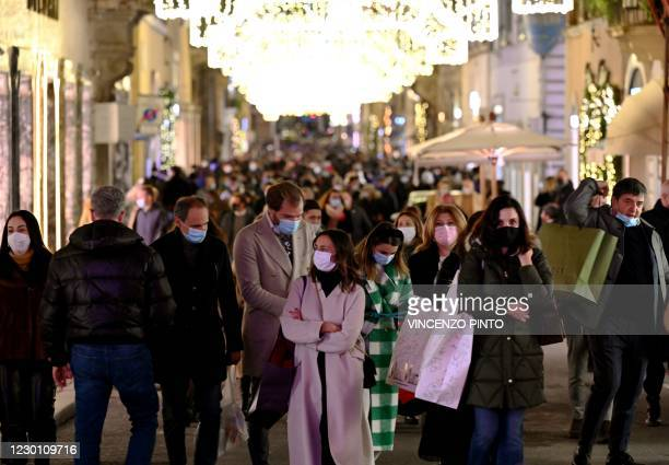People wearing a face mask go about Via dei Condotti in central Rome for their Christmas shopping on December 13 during the COVID-19 pandemic caused...