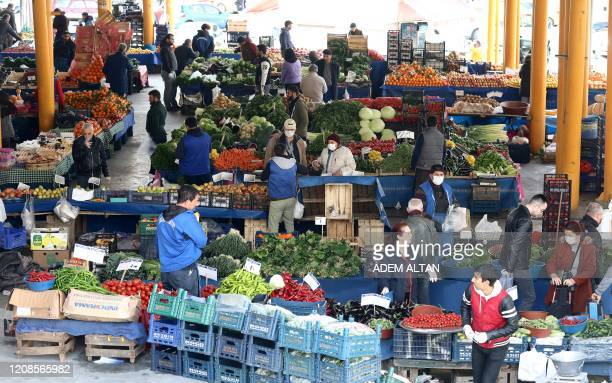 People wearing a face mask shop at the symp market in Ankara on March 29, 2020. - Outdoor fruit and vegetable markets are open in Turkey although...