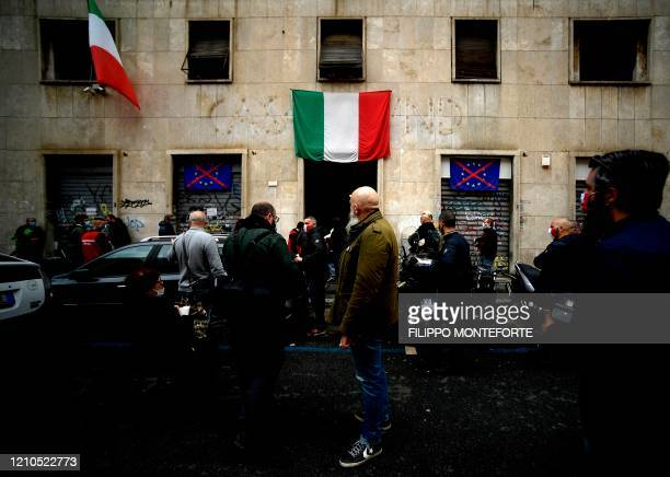 People wearing a face mask wait outside premises of Italian neo-fascist movement Casapound during a free distribution of food items on April 21, 2020...
