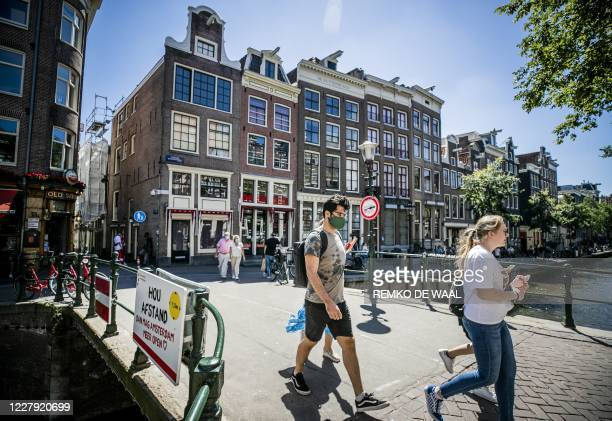 People wearing a face mask walk on a bridge of the Red Light district in Amsterdam on August 5 as from today wearing a face mask is mandatory in five...