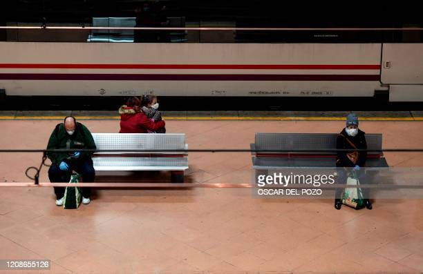 People wearing a face masks sit on benches on a platform of Atocha railway station in Madrid on March 30 during a national lockdown to prevent the...