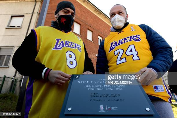 People, wearing a Kobe Bryant jersey pose near the commemorative plaque during the inauguration ceremony of a square named after late Los Angeles...