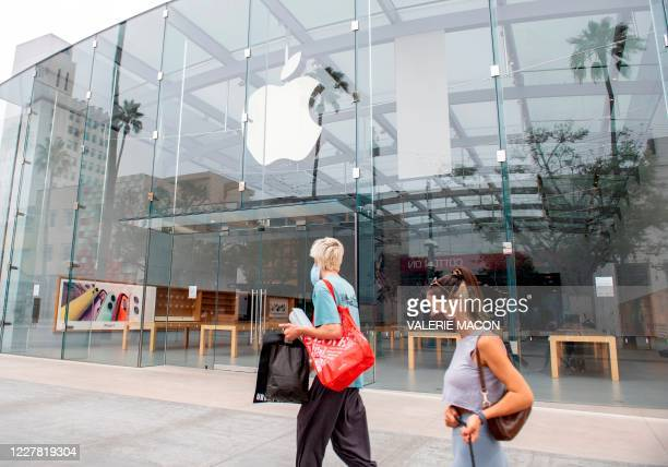 People wearing a mask walk by a closed Apple Store in Santa Monica, California, on July 28 amid the coronavirus pandemic.