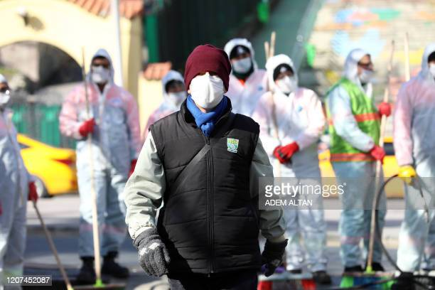 People wearing a protective face mask walk in Ankara, on March 17 amid fears of the Covid-19 outbreak. - COVID-19 has now killed more than 7,000...