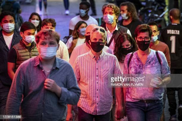People wearing a protective face mask, walk in the Red Light District in Amsterdam, The Netherlands, on August 21, 2020. - Masks are now being...
