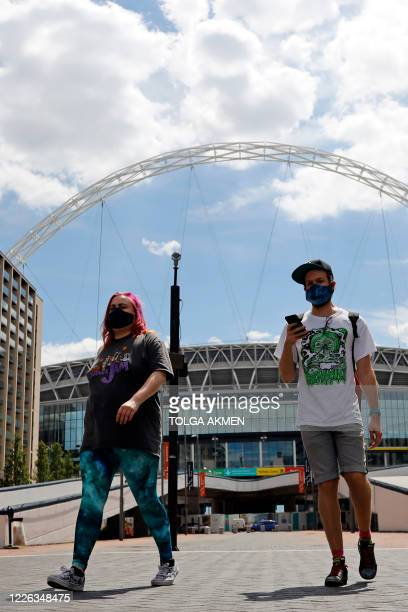 People wearing a protective face masks walk away from Wembley Stadium in London on July 12 the day that Wembley should have hosted the Euro 2020...