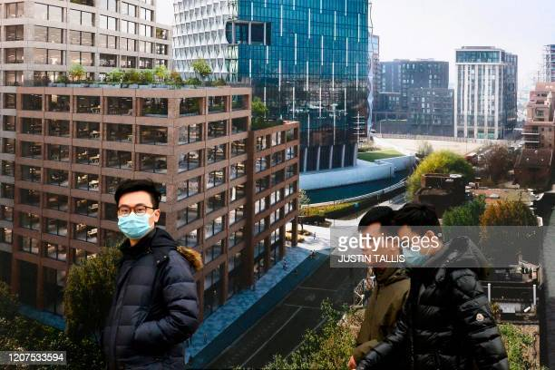 People wearing a protective face masks walk past a photograph advertising new build apartments under construction next to the river Thames in Nine...