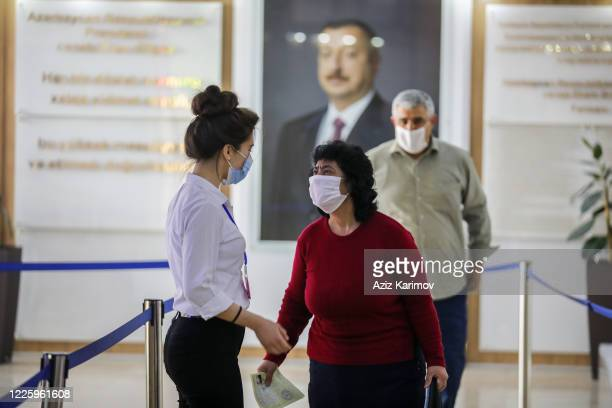 People wearing a protective facemask and keep a social distance from each other while queuing inside ASAN service and background president Ilham...