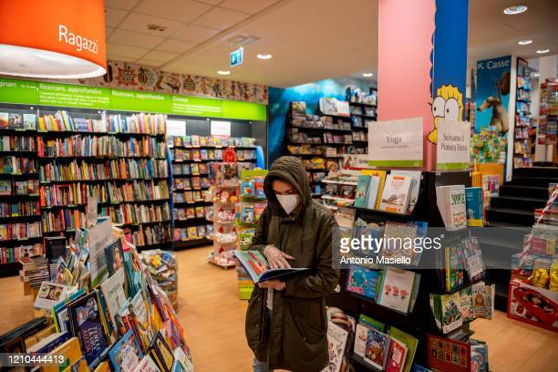 People wearing a protective mask buy books in the bookstore La Feltrinelli following the government's decision to reopen some businesses including...