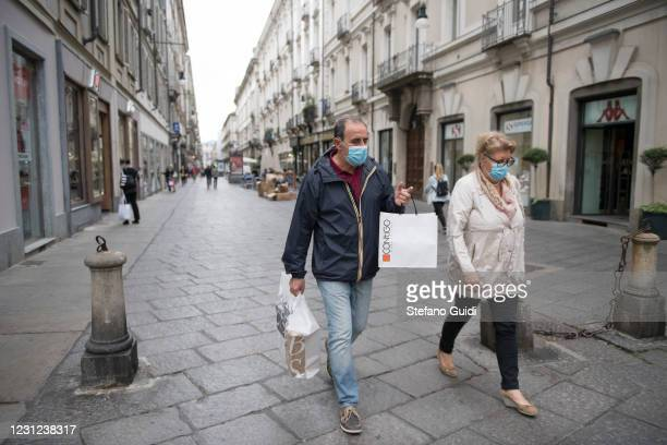 People wearing a protective mask walk in the streets of the city center after shopping in a shop on May 29, 2020 in Turin, Italy. The Piedmont Region...