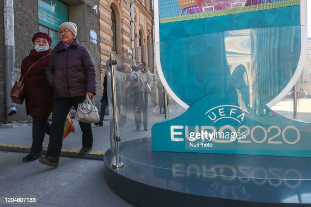 People wearing a protective mask walks near the countdown hour to 2020 in the center of St Petersburg Russia UEFA may postpone the 2020 European...