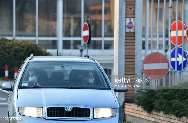 People wearing a protective repiratory mask leave in a car the municipal hospital in Codogno, southeast of Milan, on February 22, 2020. - An Italian...