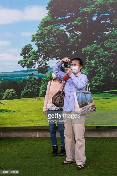 People wearing a surgical mask take pictures near the Star Ferry terminal in Kowloon on May 24 in Hong Kong China Viewed as the world's third most...