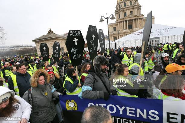 People wearing a yellow vest and carryng a sign with the name of demonstrators died during previous demonstrations walk in front of the Hotel...