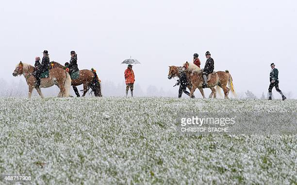 People wearing ancient and traditional Bavarian dresses take part in the St Georgi Ride on Easter Monday on April 6 during snowfall in Traunstein...