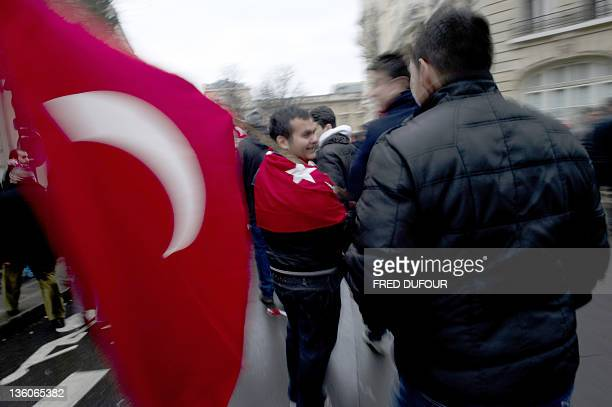 People wearing and holding the Turkish flag take part in a rally next to the French National Assembly on December 22 2011 in Paris as the French...