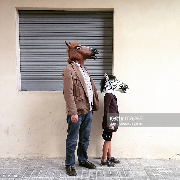 People Wearing Animal Masks Against The Wall