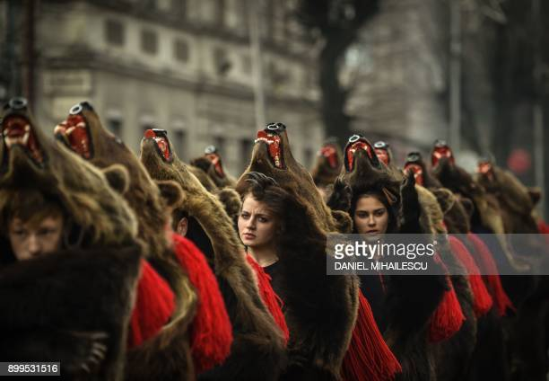 People wearing bear skins parade as part of a new year and winter festival during which groups from northern Romanian villages are invited to sing...