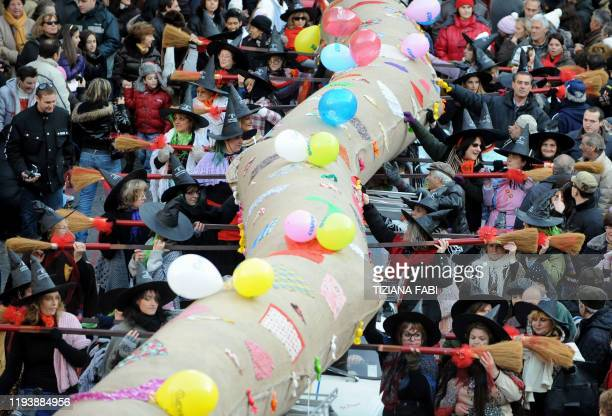 People wearing Befana outfits take part in the annual Befana parade in Viterbo on January 5 on Epiphany Eve A 52 metres long stocking is carried by...