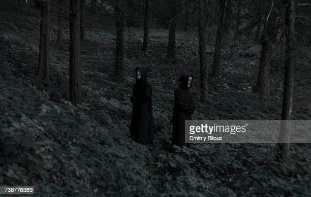 People wearing black robes and white masks in forest