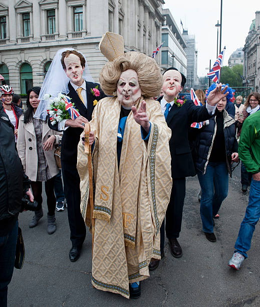 People Wearing Cardboard Masks Of Nick Clegg Margaret Thatcher And David Cameron Among The Crowds