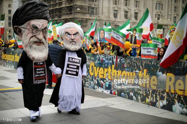 People wearing caricature masks of Iranian Supreme leader Ali Khamenei and President Hassan Rouhani participate in a rally hosted by The Organization...