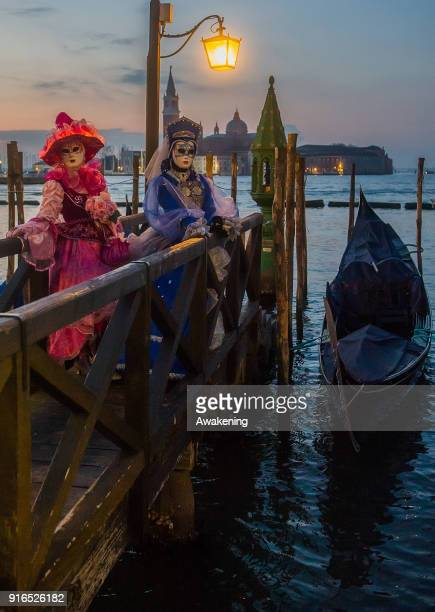 People wearing carnival costumes pose in Riva degli Schiavoni on February 10 2018 in Venice Italy The theme for the 2018 edition of Venice Carnival...