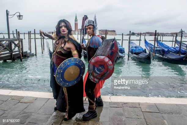 People wearing carnival costumes pose in St Mark's Square during the 2018 Venice Carnival on February 3 2018 in Venice Italy The theme for the 2018...