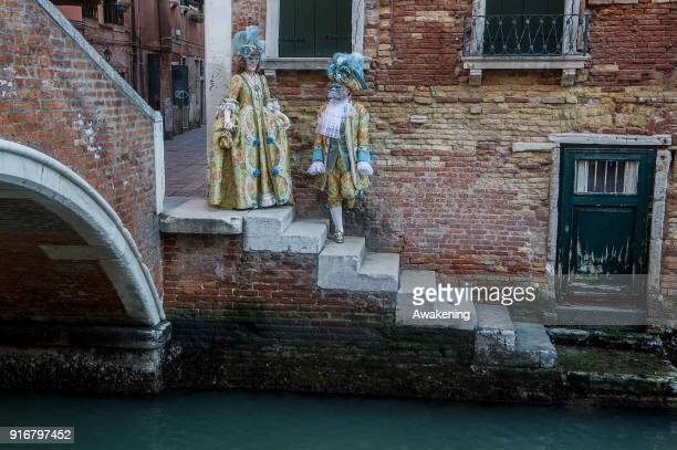 People wearing carnival costumes pose on February 10 2018 in Venice Italy The theme for the 2018 edition of Venice Carnival is 'Playing' and will run...