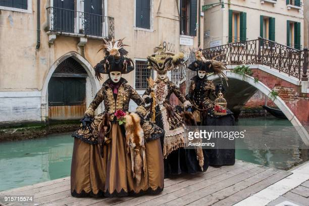 People wearing carnival costumes pose on February 8 2018 in Venice Italy The theme for the 2018 edition of Venice Carnival is 'Playing' and will run...