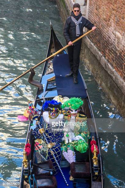 People wearing carnival costumes sail a canal on a gondola on February 10 2018 in Venice Italy The theme for the 2018 edition of Venice Carnival is...