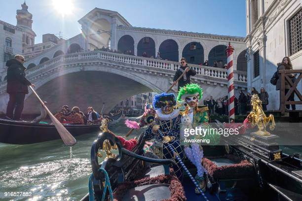 People wearing carnival costumes sail the Grand Canal near Rialto bridge on a gondola on February 10 2018 in Venice Italy The theme for the 2018...