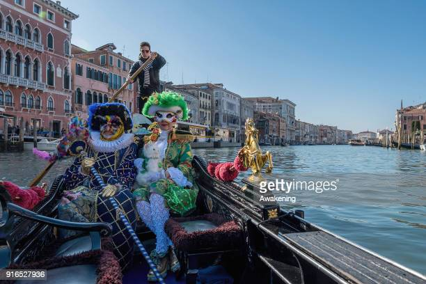 People wearing carnival costumes sail the Grand Canal on a gondola on February 10 2018 in Venice Italy The theme for the 2018 edition of Venice...