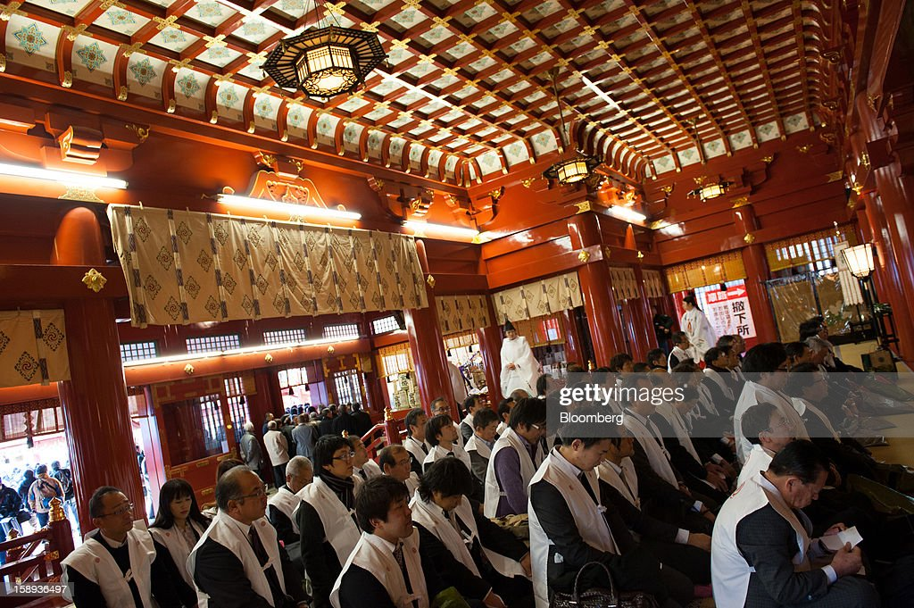 People wearing ceremonial Shinto vests sit in prayer on the first day of business in 2013 at the Kanda Myojin shrine in Tokyo, Japan, on Friday, Jan. 4, 2013. Japan's deflation-plagued economy has contracted 7 percent since 2007 as six prime ministers, including Shinzo Abe in his first term, failed to reverse the course. Photographer: Noriko Hayashi/Bloomberg via Getty Images