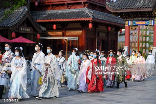 People wearing Chinese traditional clothing of the Han ethnic group walk at Changsha Fantawild Oriental Heritage theme park amid the coronavirus...